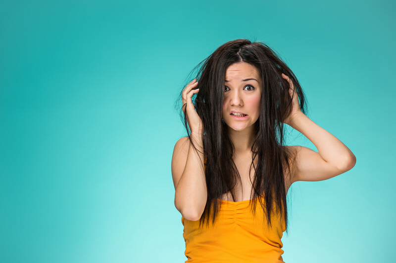 Frustrated young woman having a bad hair, wondering if her scalp is causing bad hair growth.