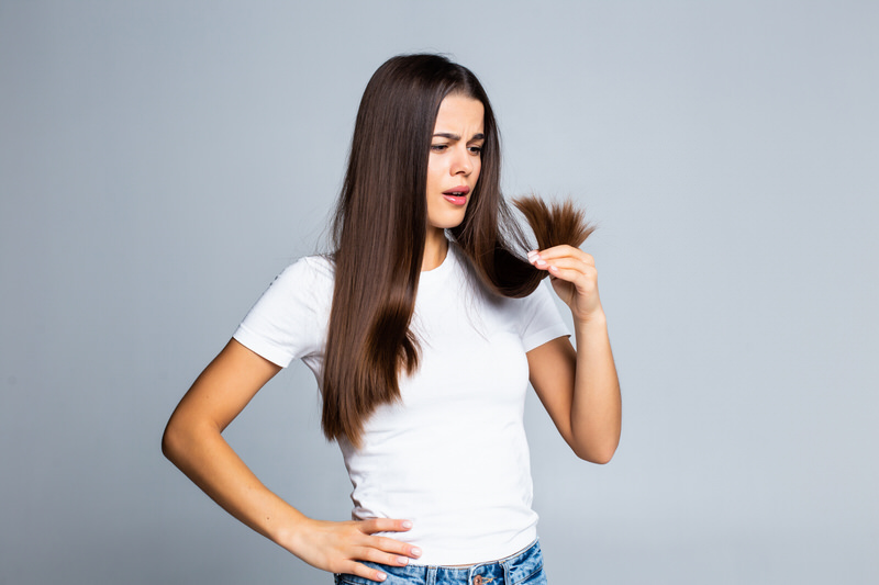A girl looking at her hair, wondering why it isn't growing fast enough.