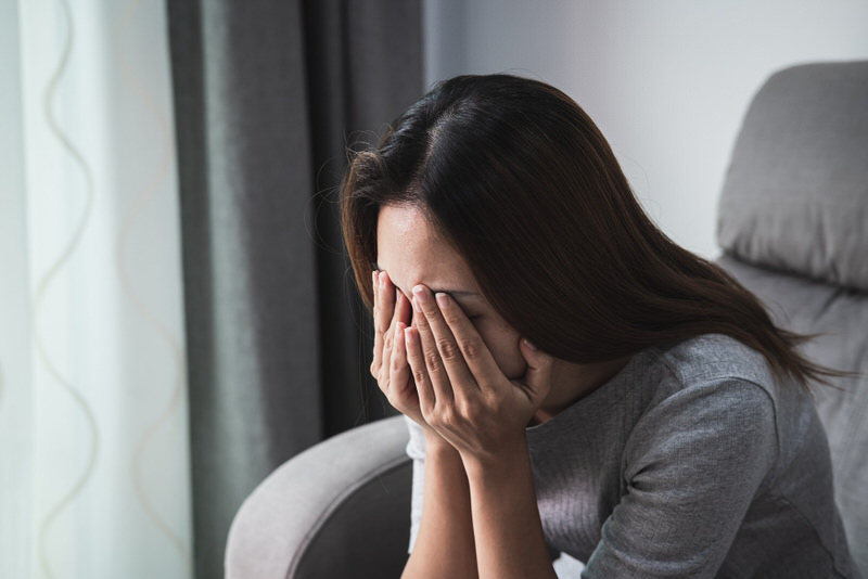 A young woman is feeling depressed, with her hands on her face, and is considering taking Phenibut to help relieve her symptoms.
