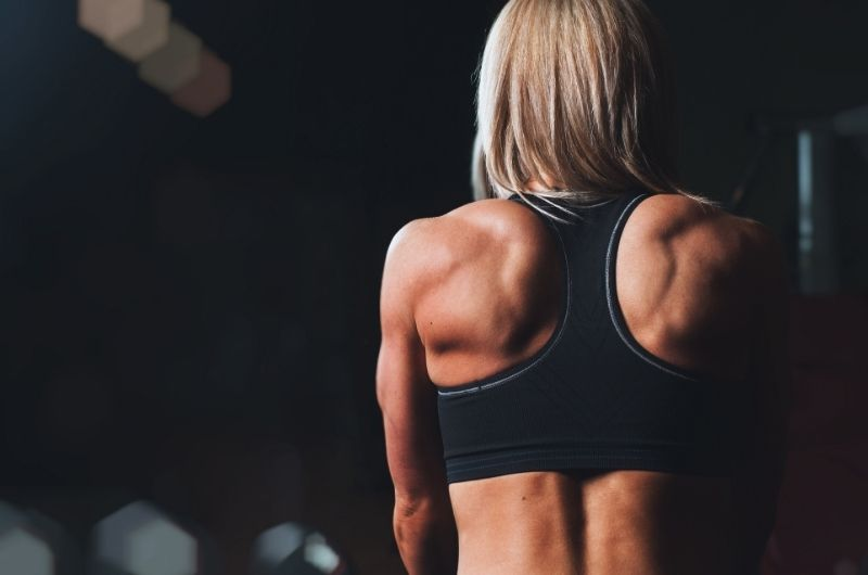 Young woman working out, and you can see the definition in her back. She makes sure to get her daily protein intake to keep building and repairing her muscles.