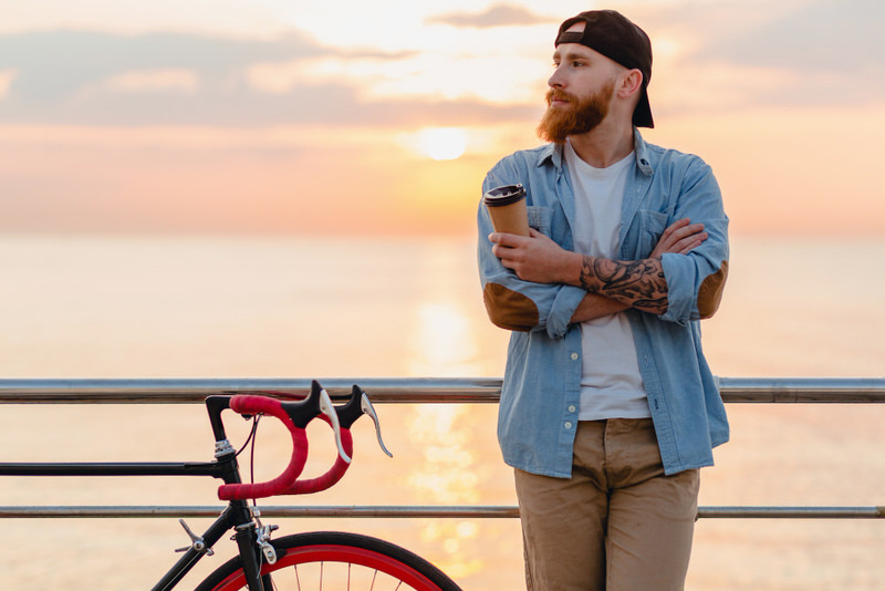 A young man takes a coffee break after his cycling exercise.