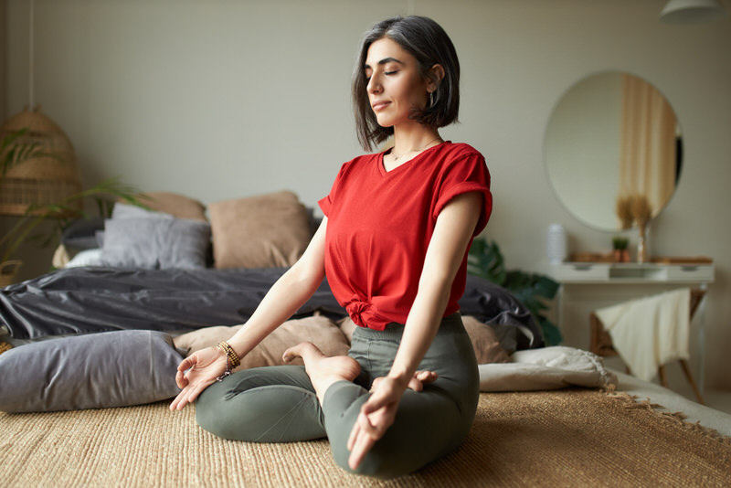 A young woman is meditating on the ground with her eyes closed.