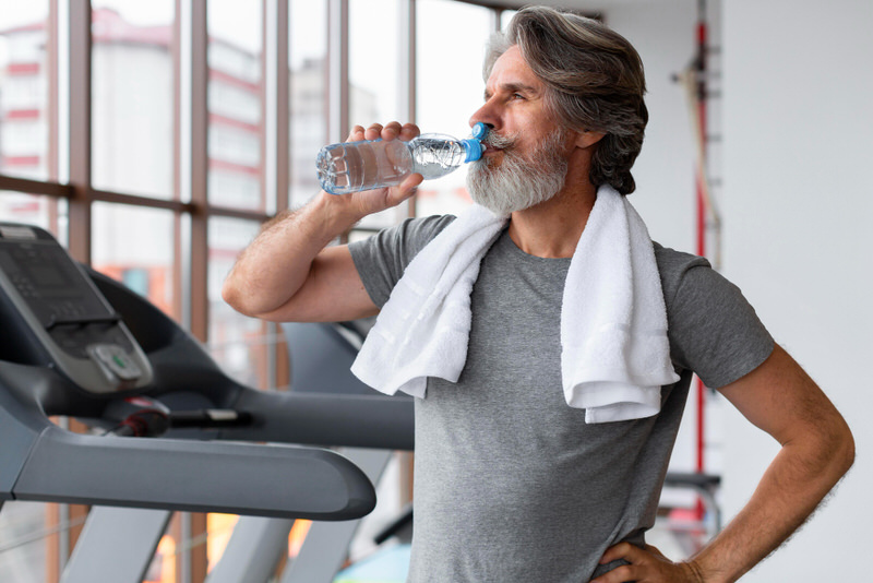 A man in his 50s is drinking some water after doing some running on a treadmill at the gym.