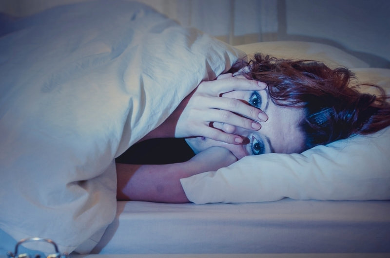 A young woman is wide awake late at night, in her bed, because she had too much caffeine.
