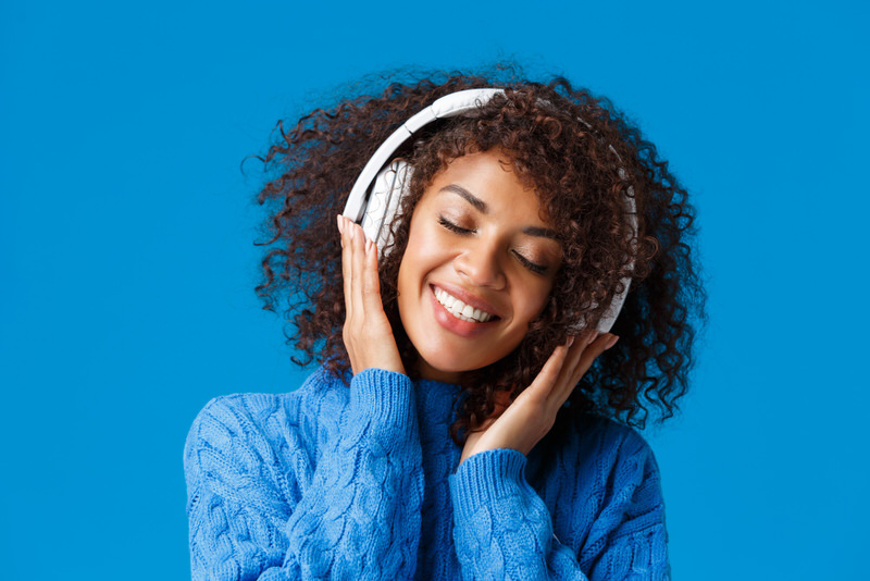 A young female is listening to wellness music on her wireless headphones