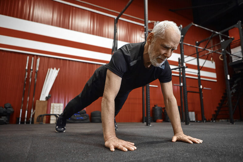 An man in is 60s is committed to working out and staying fit, and is doing some pushups to build endurance and strength.