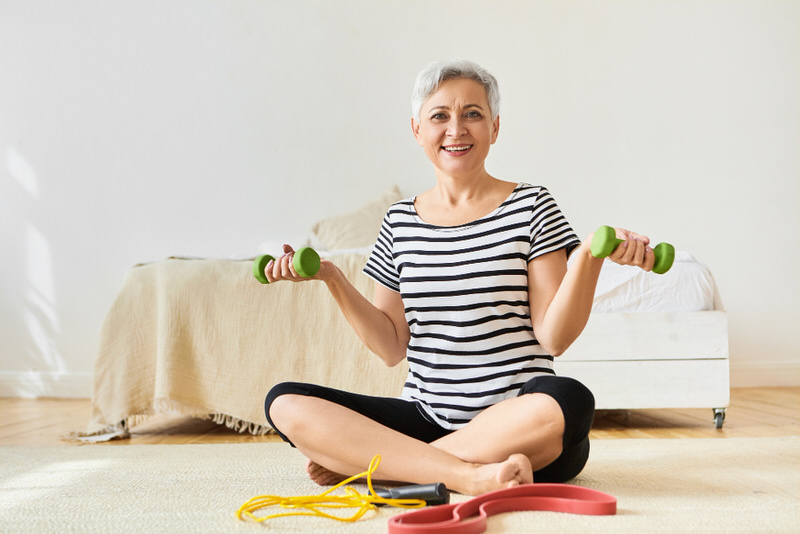 A woman in her 60s is on the ground reviewing her workout equipment, so she can start working out and build her strength safely and gradually.