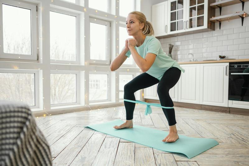 A young woman in her 50s is on a yoga mat, doing resistance band exercises to build her core.