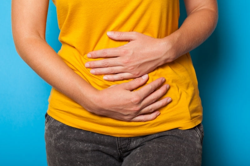 A young woman is clenching her stomach because she is feeling constipated after drinking almond milk.