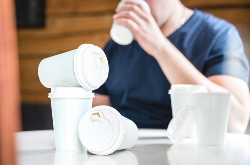 A young man is sitting and working, drinking his 6th cup of coffee. He is overdosing on caffeine and will feel the negative effects of it.