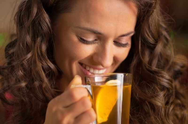 A young woman is drinking chamomile tea as an alternative to coffee, to reduce her nausea.