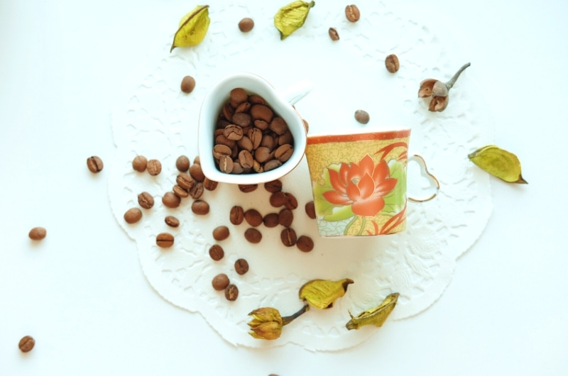 Coffee beans in a cup, and scattered on a table.