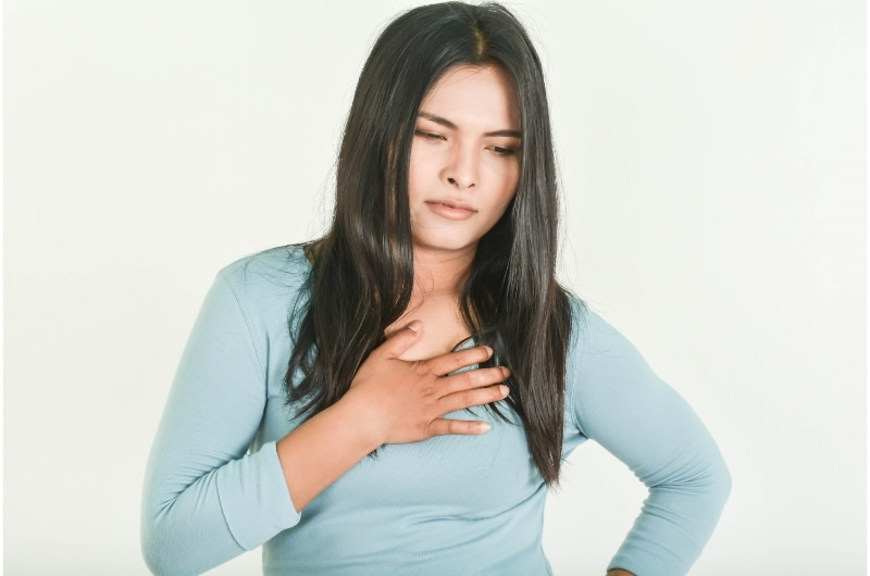 A young woman is having heartburn pain after drinking coffee.