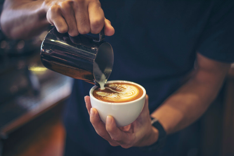 A barista is making a cappuccino with milk and sweetner.
