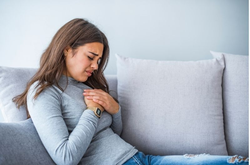 A young woman is having heartburn pain.