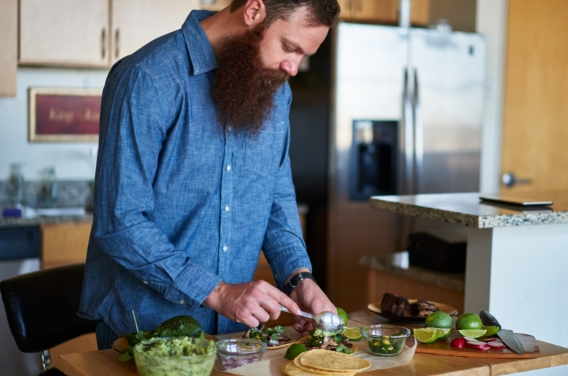 A young man is making tacos with guacamole for his healthy dinner.