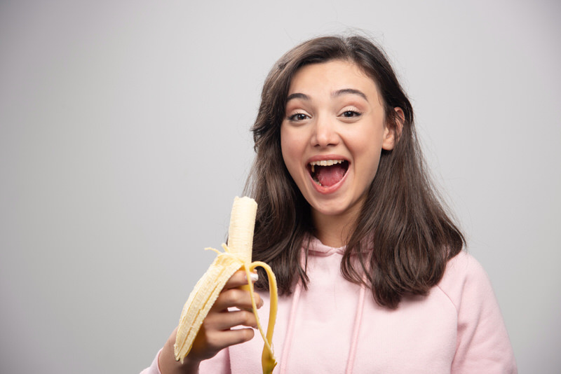 A young woman is eating a banana and smiling.