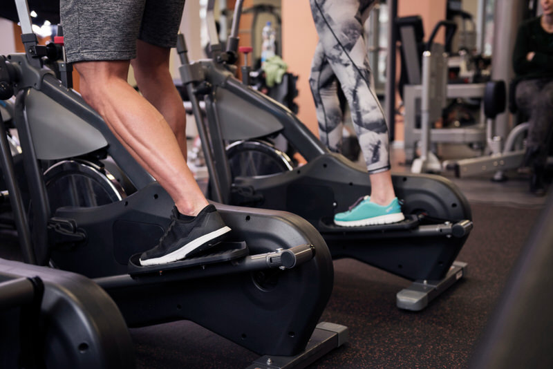 A young couple is working out on the elliptical together, using it in the reverse motion.