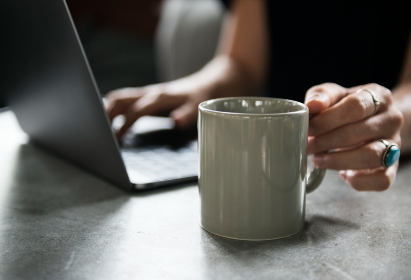 A young woman is working in a cafe and drinking black coffee.