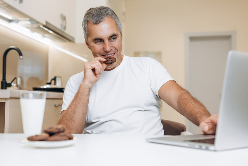 A middle-age man is eating chocolate before his upcoming colonoscopy.