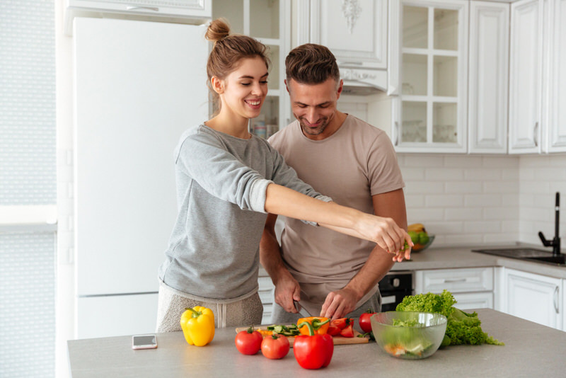 A young couple is preparing a healthy salad together as part of their safe and healthy low-calorie diet.
