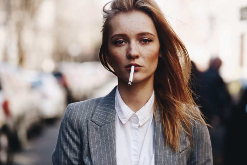 A young woman in work attire is smoking outside during her work break.