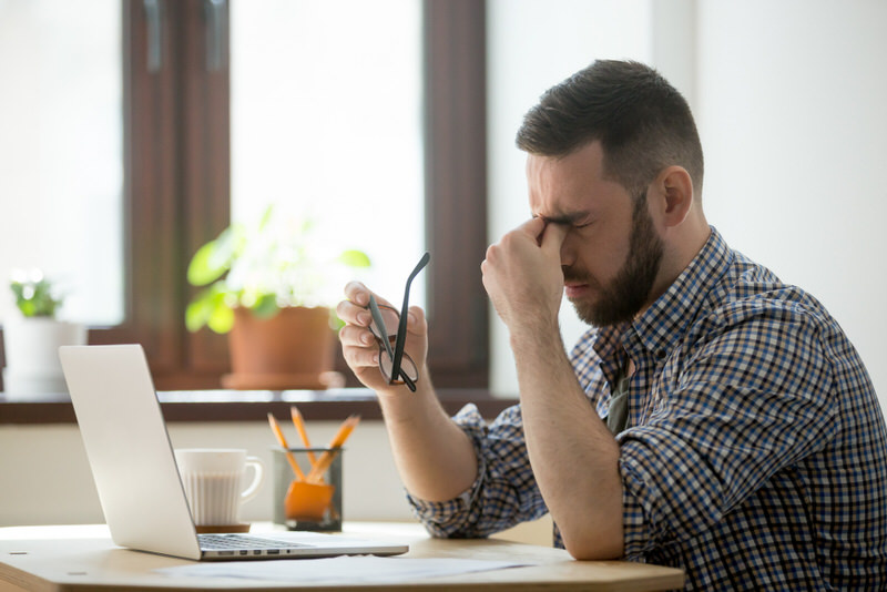 A young man is stressed out from working and is getting a pulsating feeling from below his eyes.