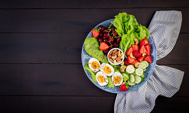 A healthy bowl of salad, nuts, and eggs.