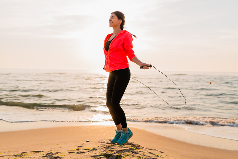 A woman jumping ropes by the beach as her daily exercise to burn calories.