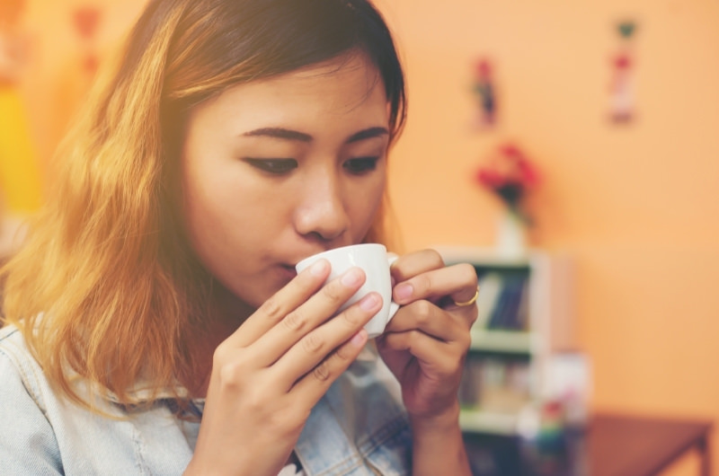 A young woman is drinking green tea to help reduce her night sweats.