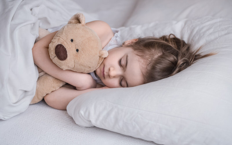 A toddler girl is sleeping in her bed after drinking her Ovaltine.