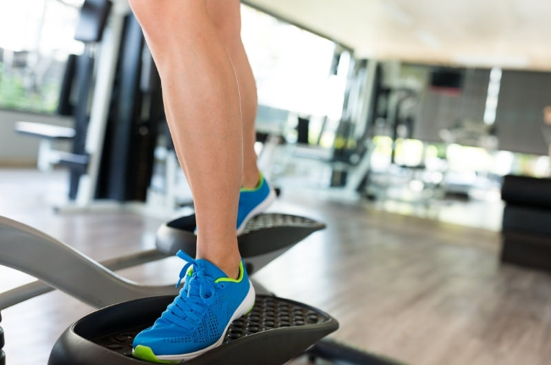 A man is using the elliptical on reverse, to work out a different part of his legs.