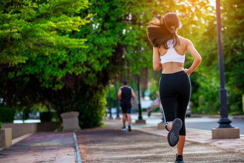 A young woman is running by the park as her daily exercise.