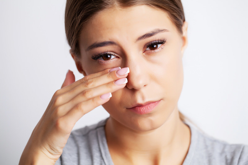 A young woman is having pain from severe eye twitching.