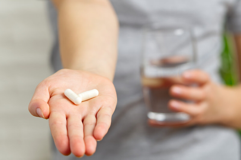 A young woman is holding out 2 vitamins on her palm, double the amount of what her recommended daily dosage is.