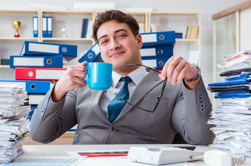A young man is working at the office, overwhelmed with the amount of work, and is drinking too much coffee in one day.