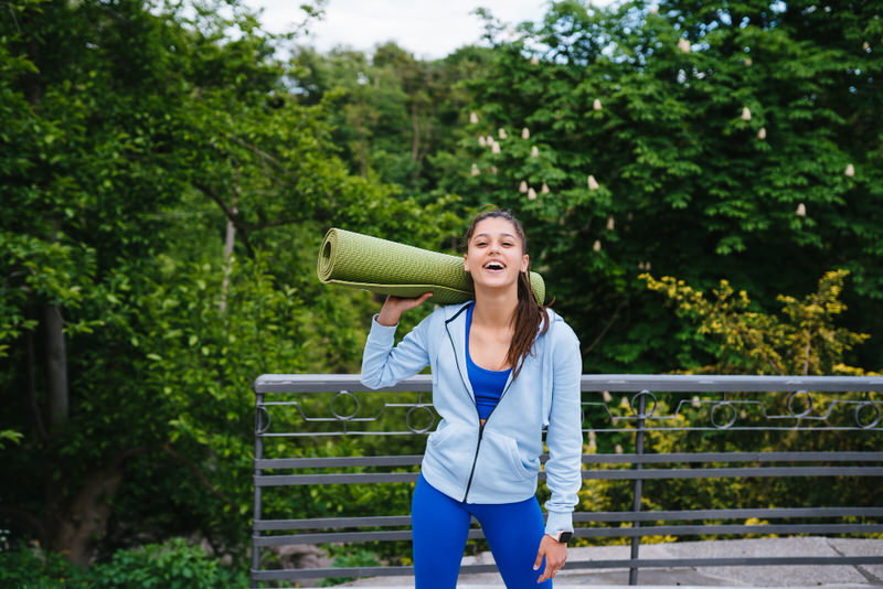 A young woman is holding her yoga mat and is ready to do some yoga outside.