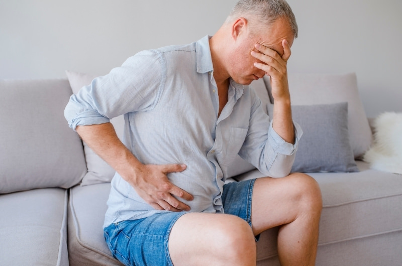 A middle aged man is sitting on the sofa clenching his right side of his stomach because of sharp pain, a possible sign of Appendicitis.