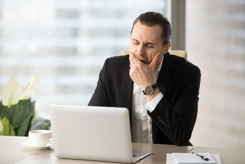 A businessman is yawning because he's tired from not sleeping well.