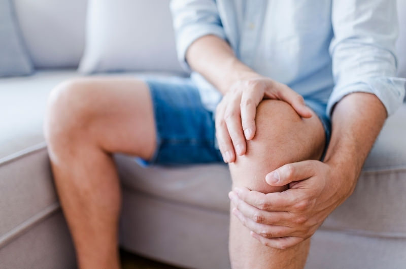 A man is sitting on the sofa and massaging his knee because he can't bend it more than 90 degrees.