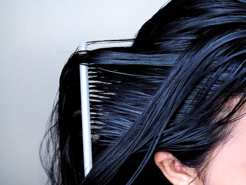 A woman is combing through her waxy hair.