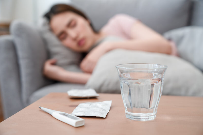 A young woman is laying down on the sofa after taking some medication for her recurring strep throat.