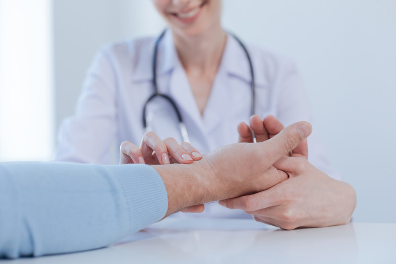 A man with wrist pain is at the doctors to get it examined.