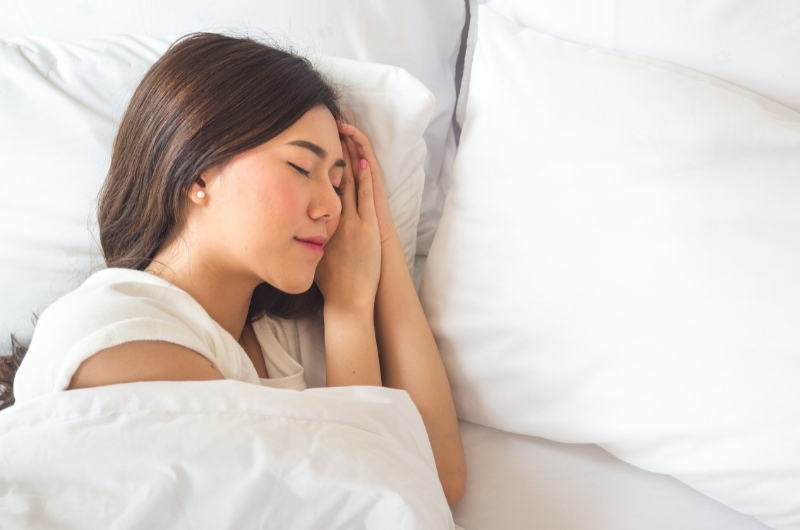 A young woman is sleeping on her left side.
