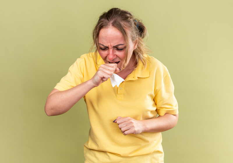 An unhealthy older woman is coughing a lot, possibly because of her smoking habits.
