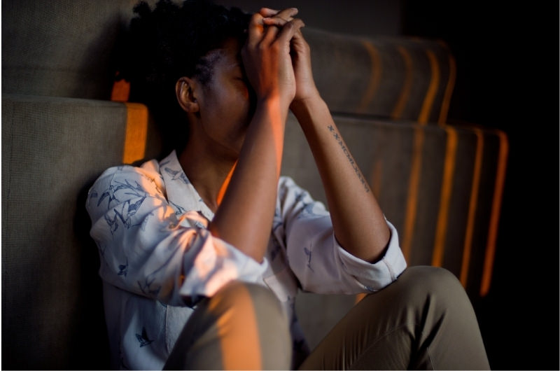 A stressed-out young woman is sitting in the dark thinking and isn't feeling hungry at all.