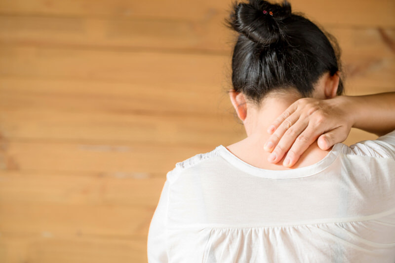 A middle-aged woman who has shingles is constantly itching her back and neck.