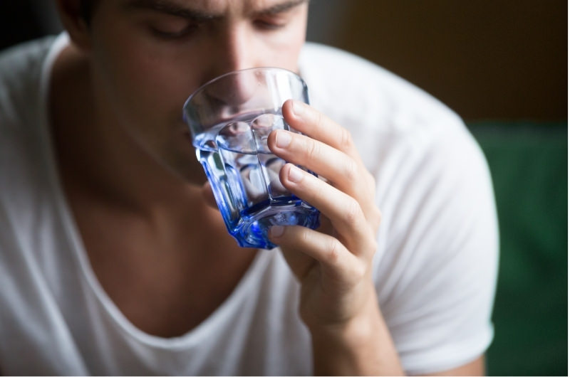A young man is drinking water from a glass, wondering why it's tasting slightly sweet to him.