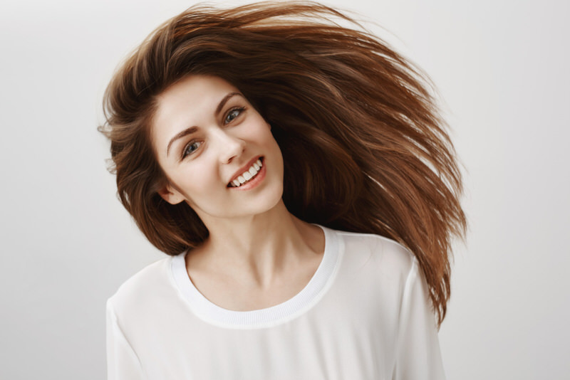 A young woman is smiling and showing off her healthy hair and scalp.
