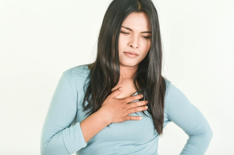 A woman is holding her chest after feeling pain in the area due to her acid reflux.